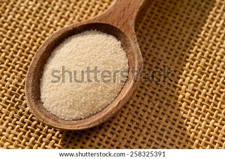 White semolina grains kasha portion on wooden spoon closeup lying on table mat, coarsely grains healthy raw food heap in day light, horizontal orientation, nobody.  - stock photo