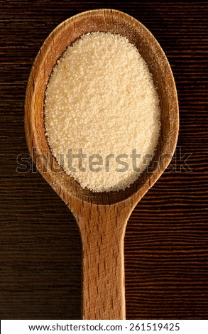 White semolina grains pile portion on wooden spoon closeup lying on dark board, coarsely grains healthy raw food heap in day light, vertical orientation, nobody. - stock photo