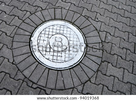 White sewer manhole marked with B sign on the cobblestone road - stock photo