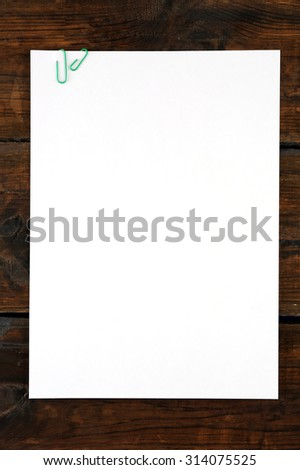 White sheet of paper attached on wooden background
