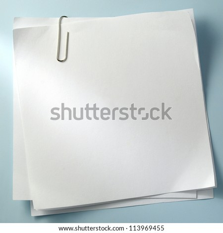 white sheet of paper for notes and paper clip - stock photo