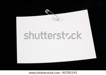 white sheet on a black background with a pin