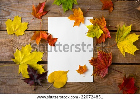 White sheet on a wooden background with autumn leaves - stock photo