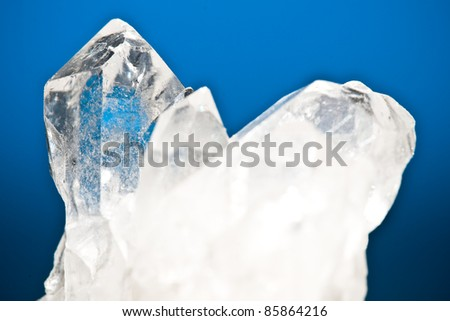 white shining rock mountain crystall quarz on blue ground - stock photo