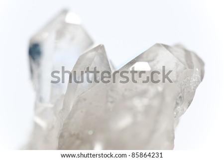 white shining rock mountain crystall quarz on white ground - stock photo