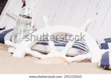 White ships wheel buried in sand with a hurricane lamp and canvas in front of the upended deck of a wooden boat in a depcition of a shipwreck, still life of models or toys - stock photo