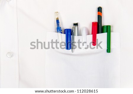 white shirt pocket with colored pens and pencils