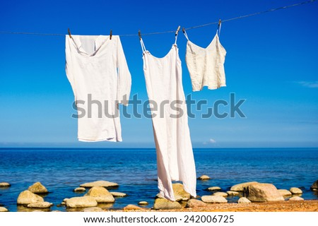 White shirts hanging on a rope on the seashore - stock photo