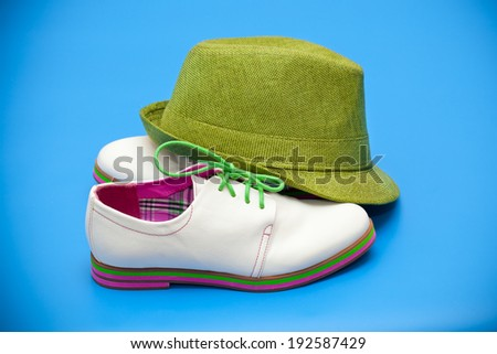 white shoes and green hat on a blue background - stock photo