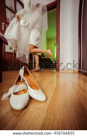 White shoes stand on the floor while bride takes a wedding dress on the background