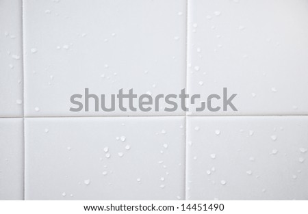 White shower tiles with evaporating water droplets