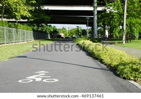 White Sign of Bicycle lanes on asphalt road in the park.