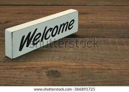 White Sign Welcome On The Rough Wood Table, Close Up, Concept, Top View - stock photo