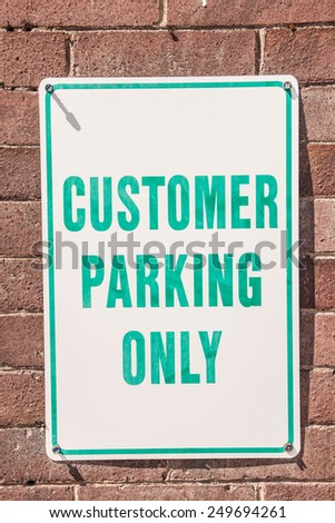 White sign with green letters for customer parking only - stock photo