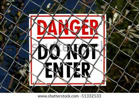 White sign with Red and Black writing saying Danger Do Not Enter and attached to a wire fence. There are spiders webs and plant material on the fence and sign - stock photo