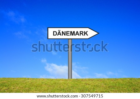 White signpost on green grass showing Denmark in german language in front of blue sky