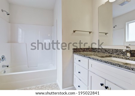 White simple small bathroom with bathtub and sink.