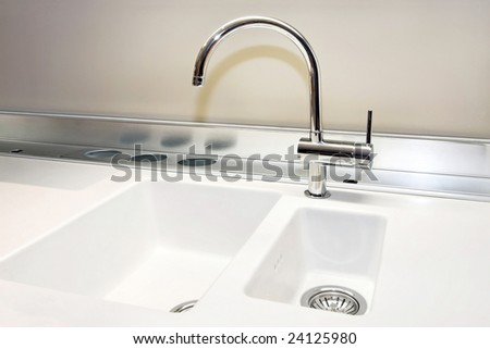 White sink and stainless still faucet in kitchen
