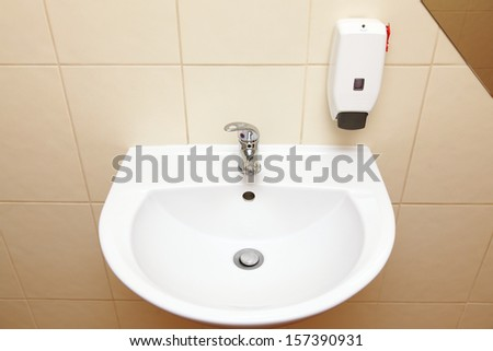 White sink tap and liquid soap in the bathroom
