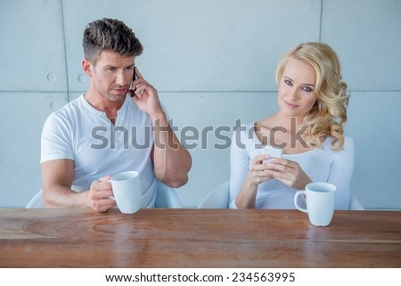 White Sitting Couple in Casual Clothing Having Coffee at the Wooden Table While Busy with their Own Mobile Phones. - stock photo