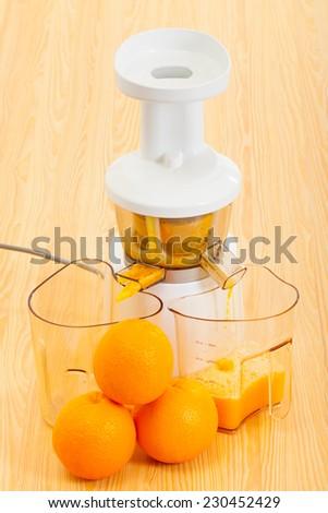 white slow juicer makes delicious fresh orange juice - stock photo