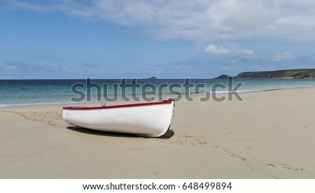 White small boat on beach at Sennen Cove in summer, Cornwall, England.