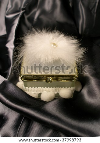 white small box for rings with a powder-puff from above