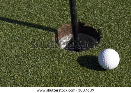 White Small Golf Ball Next To The Hole On The Green - stock photo