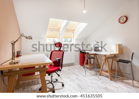 White small office with wooden desks at the attic in big residence