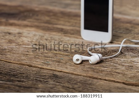 White smart phone with earphones and isolated screen on old wooden desk. - stock photo
