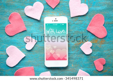 White smart phone with hearts on wooden desk. - stock photo