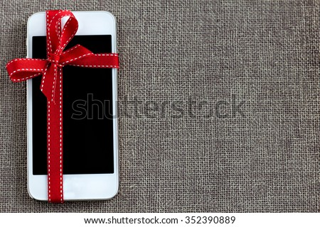 White smart phone with isolated screen on the contrast textile background - stock photo
