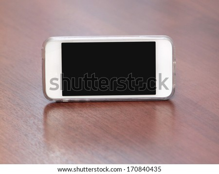 White smart phone with isolated screen on wooden desk - stock photo