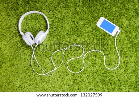 White smartphone and headphones, on the green carpet. - stock photo