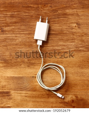white smartphone charger over wooden board - stock photo