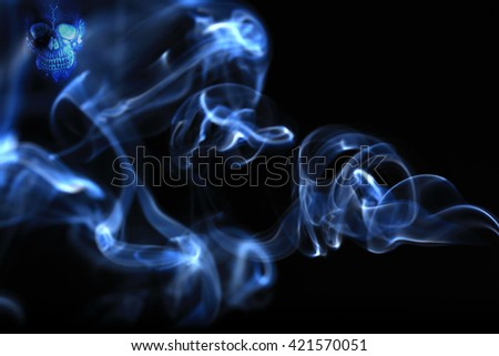 White smoke cigarette and skull on a black background - stock photo