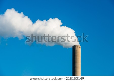 White smoke clouds from a high concrete chimney against a clean blue sky on a sunny day in the summer season. - stock photo