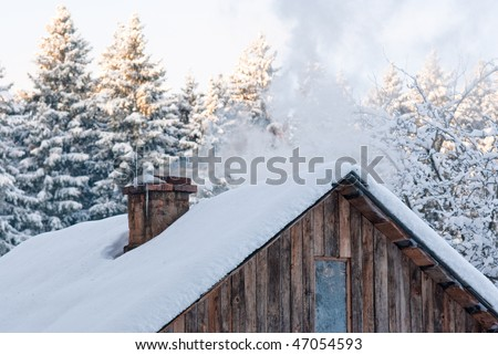 White smoke comes out of a house's chimney on a winter day in russian village - stock photo