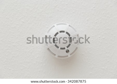White smoke detector on ceiling in closeup - stock photo