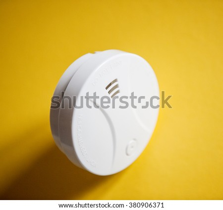 White smoke detector on yellow table. smoke detector is a device that senses smoke, typically as an indicator of fire - stock photo
