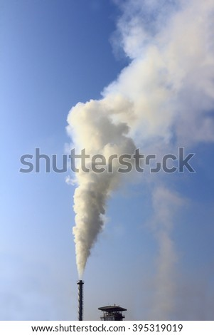 White smoke from factory chimneys , timber industry on blue sky . - stock photo