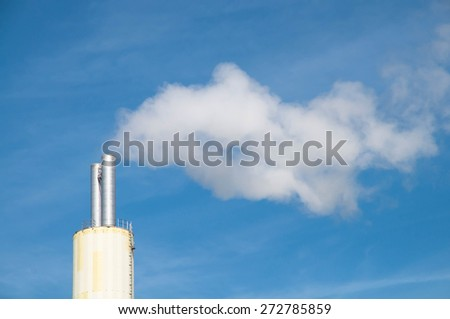 White smoke out of a stack of a waste incineration plant - stock photo