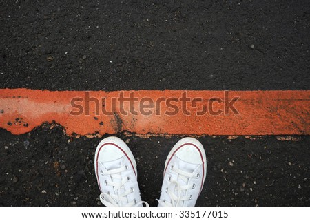 White sneaker shoes standing behind the red line. Canvas shoes on street. Top view. - stock photo