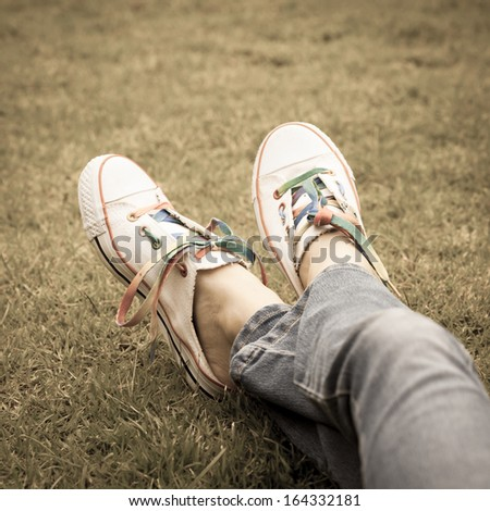 white sneakers on girl legs on grass during sunny serene summer day. - stock photo