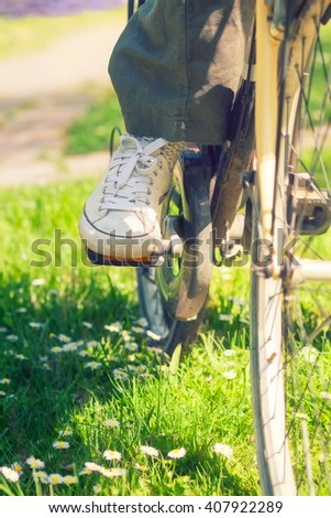 White sneakers on woman's legs on a bike during sunny summer day, in a park.