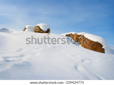 white snow covering boulders on the hill - stock photo