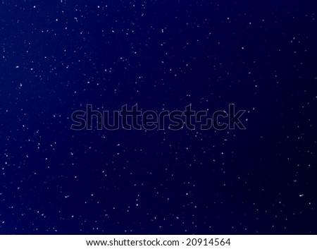 White snow in the dark blue night sky - stock photo