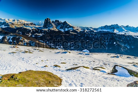 White snowy Dolomites mountains with rocks, snow-capped peaks and green conifers in winter