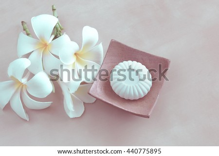 White soap on wood soap plate and white Plumeria flower in vintage background. - stock photo