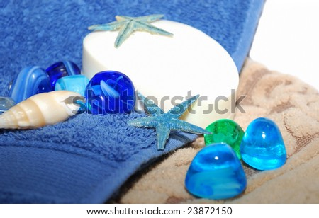 White soap with blue sea stars and shells are on the blue towel.